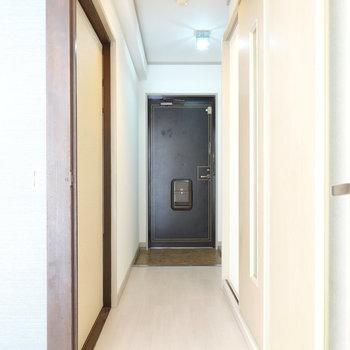 リビングから玄関を。左が洋室、右が脱衣所です。トイレは奥の玄関横にあります。(※写真は5階の反転間取り別部屋のものです)