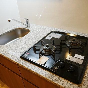 キッチンは天板が石目調で高級感漂います(※写真は4階の反転間取り別部屋のものです)