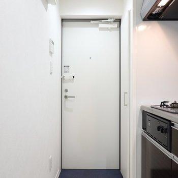 玄関はキッチンの横に。靴箱は右の壁に埋め込まれています。(※写真は1階同間取り別部屋のものです)