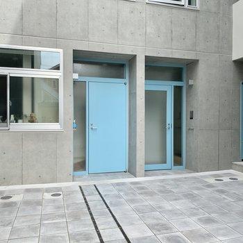 とてもきれいで広い共用部に水色の扉が並びます。