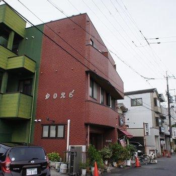 赤レンガと緑のツートーンカラーが不思議なマンション。