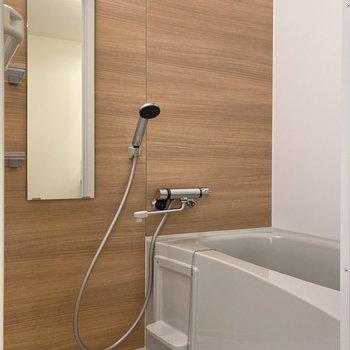 木目調のパネルが安らぎをもたらすバスルームでじっくり入浴を。