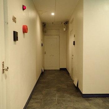 共用部】モノトーンのスタイリッシュな廊下。右を向くと、