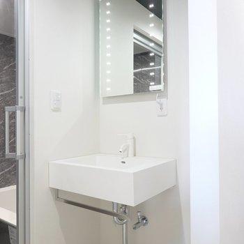 洗面台もミニマル。鏡には照明も付いていて、シンクの下はタオルバーに。(※写真は2階の同間取り別部屋のものです)
