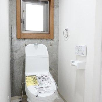 トイレはウォシュレット付き。コンクリ壁に窓の木枠が異素材ミックス。(※写真は2階の同間取り別部屋のものです)