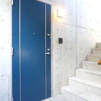 コンクリートの空間に濃いブルーのドアが映える。
