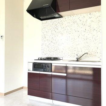 白と茶色の落ち着いた色。冷蔵庫もお隣に。(※写真は3階の同間取り別部屋のものです)
