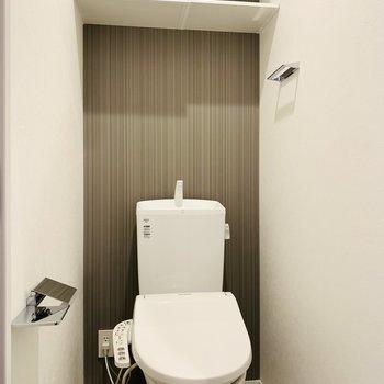 トイレは玄関スペースからのアクセス。上部には扉もついた収納棚付き。
