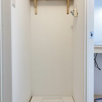 反対側には洗濯機置き場。棚には洗剤等を並べてスッキリと。