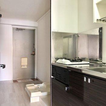 廊下にコンパクトキッチン、冷蔵庫、洗濯機置き場が並びます。