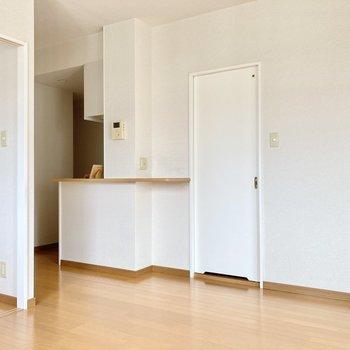 リビングの奥にあるのはキッチン!ドアの先は脱衣所です。 (※写真は8階の反転間取り別部屋のものです)