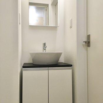 キッチンの後ろにはサニタリーがあります。洗面台の鏡の後ろは収納に。