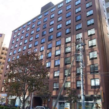 通りに面した、ビジネスビルのようなマンション。1回にはヘアサロン、歯科クリニック、コンビニが入っています。