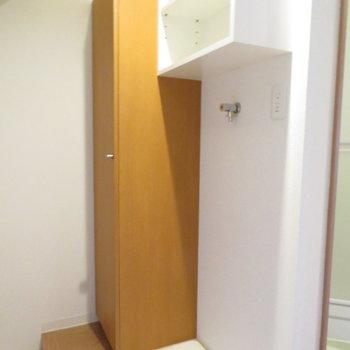 玄関すぐに洗濯機置き場が。上部には収納も(※写真は7階の反転間取り別部屋のものです)