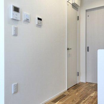 【LDK】正面には給湯機やTVモニタ付きドアホン。左にあるドアは……?