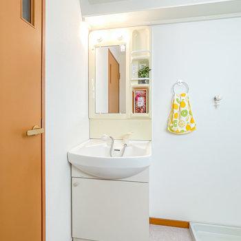 洗面台は少しレトロですが、棚付きで使いやすそう。壁の棚は洗濯用品などの置き場に◎