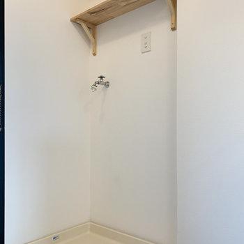 洗濯機置場は玄関横に。こちらにも洗剤などを置ける木製の収納棚を設置!