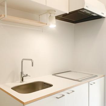 キッチンは掃除がしやすいIHコンロ。木製の吊り棚にはお気に入りのマグカップたちを。