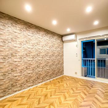 お部屋に入るとヘリンボーン柄の床とレンガ調の壁がお出迎え。その空間をダウンライトが明るく照らします。
