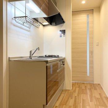 洋室を出てすぐの位置に木調の素敵なキッチン。(※写真は2階の反転間取り別部屋のものです)
