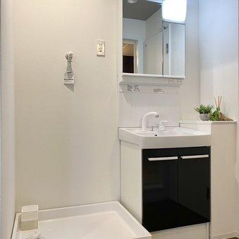 スマートな洗面台と洗濯機置き場。2つを分けるようにカーテンレールが走っていますね。※写真の小物はサンプルです