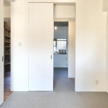 【リビング側の洋室】奥に進むと、ウォークインクローゼット、別の洋室へと繋がっています。