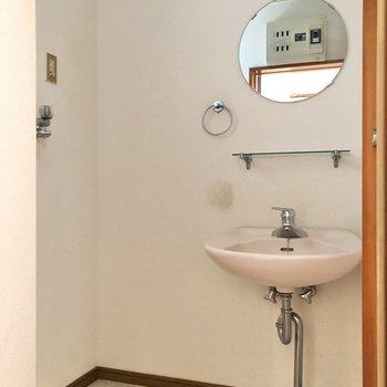 サニタリールームには丸い鏡がかわいい独立洗面台と洗濯機置き場。