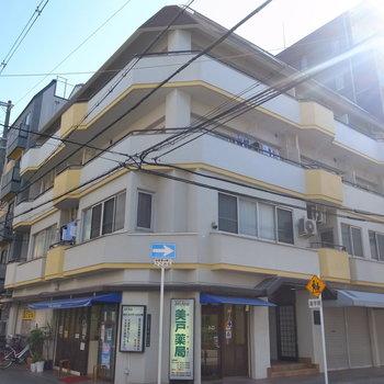 角地にある渋い外観のマンション。1階は薬局になっています。