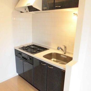 キッチンはシックにブラック※写真は11階の同間取り別部屋のものです