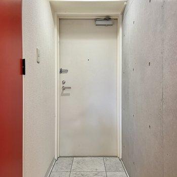 玄関は大理石調のタイルが素敵。頭上のシェルフには靴箱などをそのまま収納しましょう。