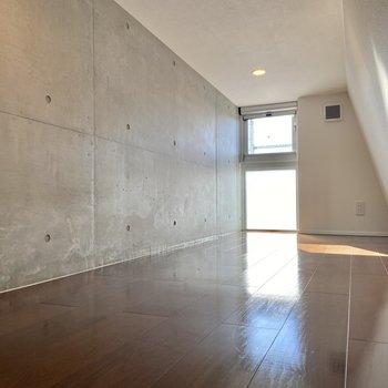 コンクリート打ちっ放しに天井を兼ねる斜めの壁が個性的!コンセントも2口×2個あるので寝室や書斎のように使ってもよさそう。