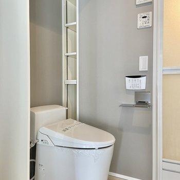 温水洗浄便座のついたタンクレス型。奥のスリムな可動棚にはお掃除グッズなども収納できます。