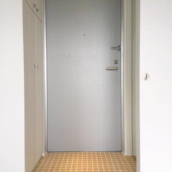 玄関。足元のタイルが可愛いですね。右の壁には姿見が備え付けられてますよ。※写真は8階の同間取り別部屋のものです