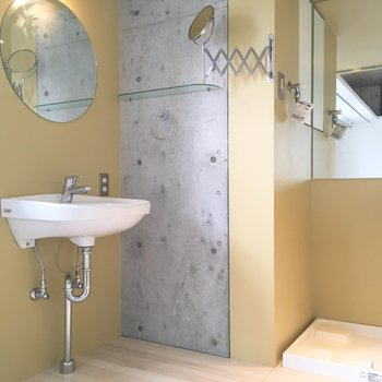洗面台と洗濯機置き場。ひょうきんな鏡が首を伸ばしてますよ〜。※写真は8階の同間取り別部屋のものです