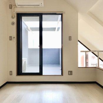 ベッドを置いて、ダラダラしたいなぁ。なんとここにもエアコン付き!あの窓の先は…(※写真は5階の同間取り別部屋、一部仕様色が異なる場合がございます)