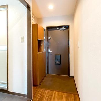 玄関はダウンライトで明るく、スペースも広め。靴箱にはちょっとした鏡も付いています。