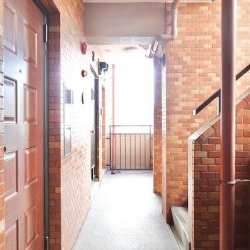 玄関前の共用部はレンガ張りの空間。エレベーターも階段もすぐ近くに。