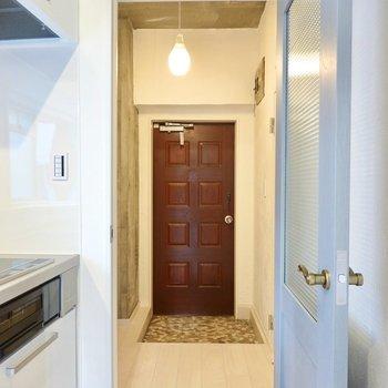 ドアを開けると雫型のペンダントが温かな玄関へ。右側にはトイレが。
