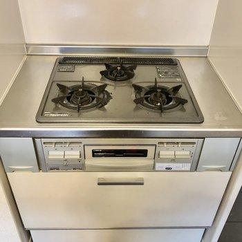 キッチンはセパレートタイプでコンロは後ろに。 3口にグリルも付いています。 (※写真は修繕前のものです)