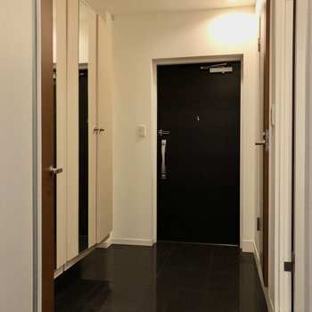 黒のタイルがかっこいい玄関周り。 段差が無いのでマットなどでうまくゾーニングしましょう。 (※写真は修繕前のものです)