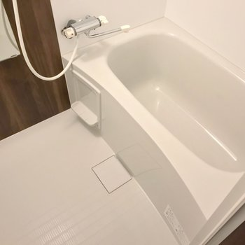 お風呂はサーモ水栓。木目のシートでリラックスできそうな雰囲気。