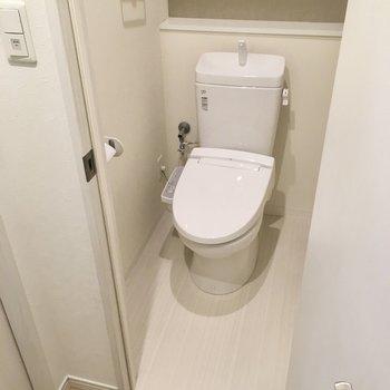 トイレはウォシュレット付き。L字の棚に小物やペーパーを。(※写真は2階の同間取り別部屋のものです)