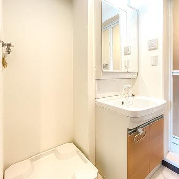 左手には洗濯機置場と洗面台。キッチンとお揃いのカラーで、鏡の裏は収納に!