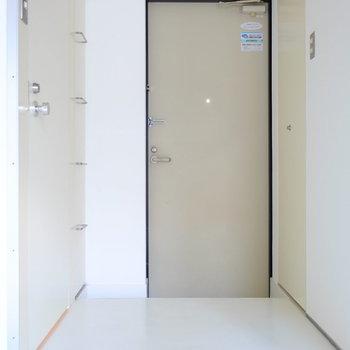 玄関も白で。左のラダーが付いた扉の中には靴箱、右の扉の中には洗濯機置場が隠されています。※写真は同間取り別部屋のお写真です