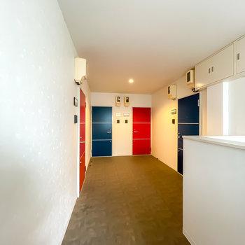 玄関前の共用部も綺麗で明るい。青と赤のドアに白い壁がまるでトリコロールのよう!