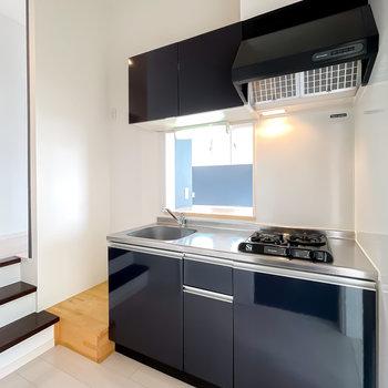 キッチンもお部屋に合わせた深いブルー。木目調の床は冷蔵庫置き場。