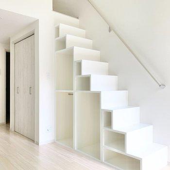 実は階段は収納!下段には、折りたたみ式家具の置き場所にしても◎ 夜はササッと片付け、ここを就寝スペースにしても。