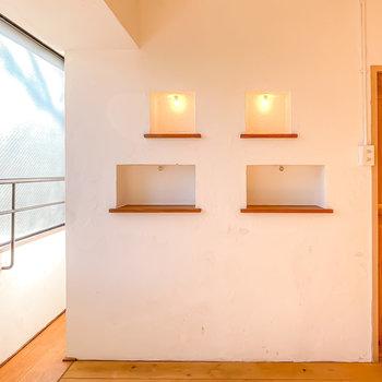 窓際の壁には柔らかい照明の付いた棚が。本当にお気に入りな物はここに飾りたい。