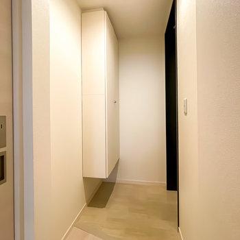ダウンライトで明るい玄関はタタキと廊下の床材の切り替えがどことなくスタイリッシュ。