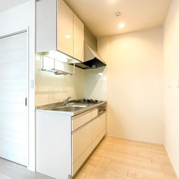 キッチンはダウンライトで明るい雰囲気。冷蔵庫やシェルフを置くスペースも広々。